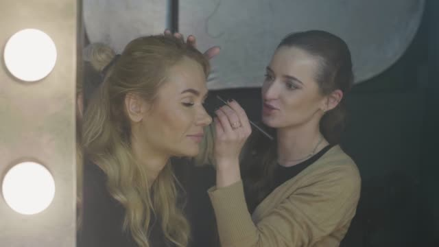 Woman visagiste applying waterproof makeup for beautiful girl in beauty salon Woman visagiste applying waterproof makeup for beautiful girl in beauty salon. Professional makeup face for video shooting and photo session mascara stock videos & royalty-free footage