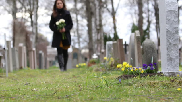 Woman visiting a grave at a graveyard