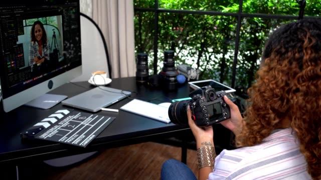 frau vlogger hält kamera für das filmen eines films oder eines video-blog im studio-büro. freiberufliches konzept . - freischaffender stock-videos und b-roll-filmmaterial