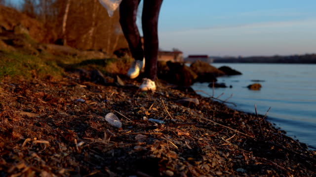 A woman volunteer collects garbage on the shore of the reservoir. video