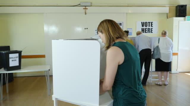 vidéos et rushes de 4k dolly: femme vote au stand au bureau de vote. élections - vote