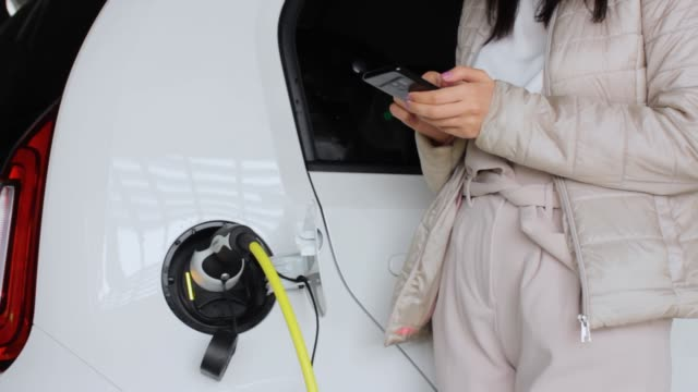 Woman waiting for recharging of electric car battery and typing on her smartphone. Eco friendly automobile. Innovative technology concept