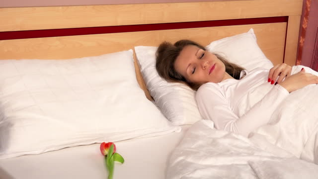woman wake up in bed and find tulip flower. happy female smiling video
