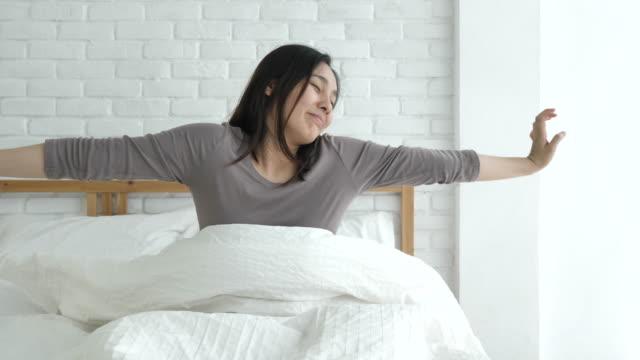 vídeos de stock e filmes b-roll de woman wake up refreshed on morning in bedroom - acordar