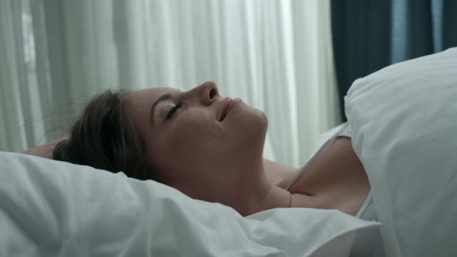 Woman waking and stretching in bed video