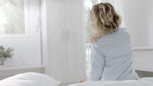 Woman waking up and having pain in shoulder and neck