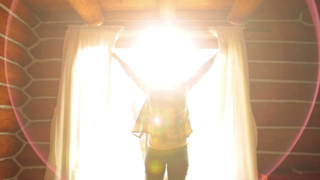 Woman waking up in a beautiful sunny morning. Silhouette of a young Woman waking up in a beautiful sunny morning. She opens the curtains and stretching in front of the window. brightly lit stock videos & royalty-free footage