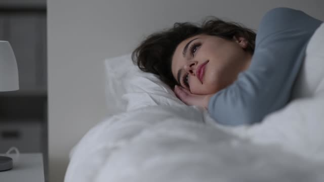 Woman waking up in her bed Young beautiful woman waking up in her bed in the morning, she is opening her eyes and smiling lying down stock videos & royalty-free footage