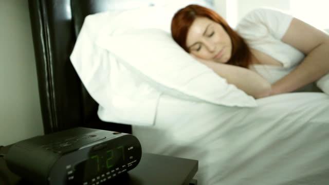 vídeos de stock e filmes b-roll de mulher acordar para um alarme relógio - dormitar