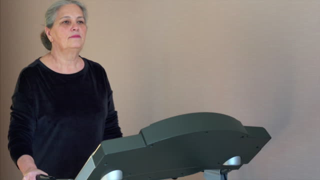 woman waling on treadmill wearing smartwatch at home. periodically check pulse. - runner rehab gym video stock e b–roll