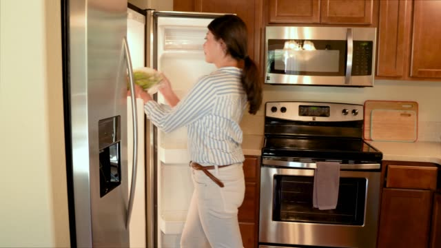 frau zu fuß in holzküche setzen lebensmittel in kühlschrank - gefrierkost stock-videos und b-roll-filmmaterial