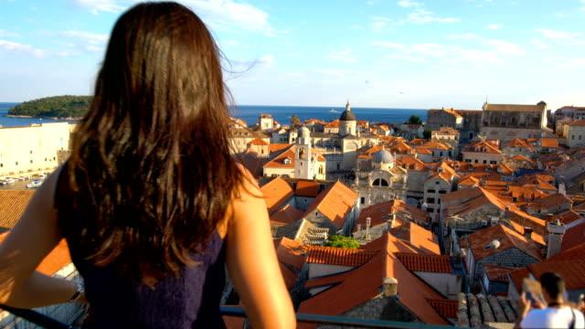 woman walk on wall of dubrovnik old town, croatia - хорватия стоковые видео и кадры b-roll