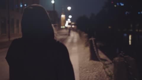vídeos de stock e filmes b-roll de woman walking alone on city street - escuro