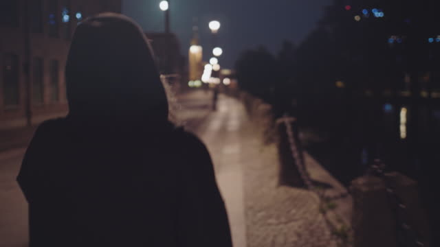 woman walking alone on city street - samotność filmów i materiałów b-roll