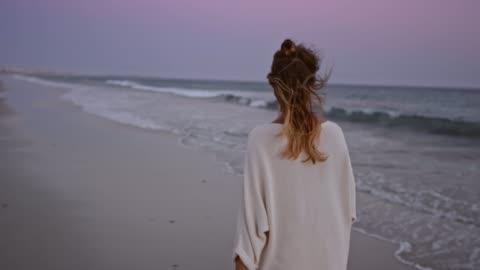 vídeos de stock e filmes b-roll de slo mo woman walking along a beach at dusk - andar