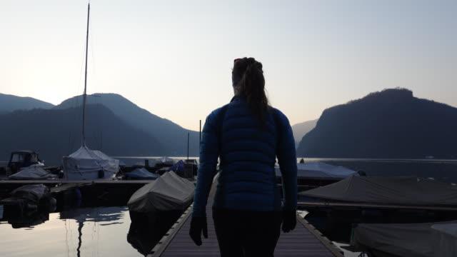 Woman walking along a dock at sunset past sailboats