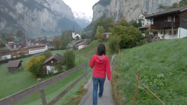 woman walking along pathway through village - время дня стоковые видео и кадры b-roll