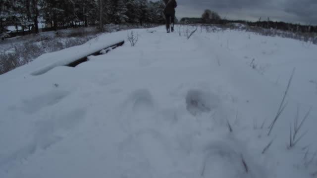 Woman walking along railway in winter