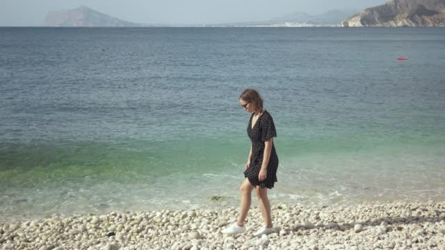 woman walking along rocky seashore looking at water - элемент здания стоковые видео и кадры b-roll