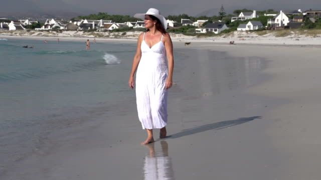 Woman walking along the water line on the beach, Cape Town,South Africa video