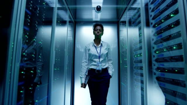 Woman walking among server racks Black woman in formal outfit walking in corridor among glowing server racks in data center it professional stock videos & royalty-free footage