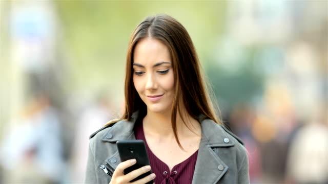 yürüyüş ve sokakta telefon arama kadın - sipariş vermek stok videoları ve detay görüntü çekimi
