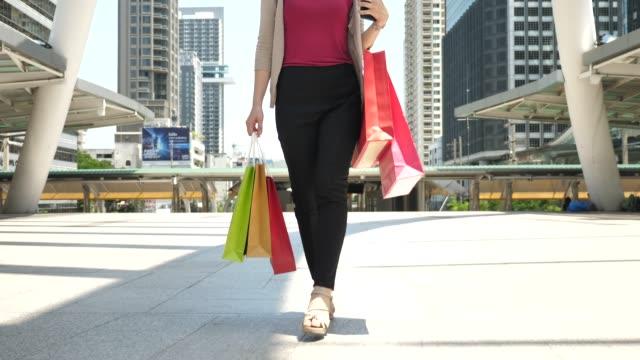 vídeos de stock, filmes e b-roll de mulher andando e dia de compras com sacola de compras - plano médio