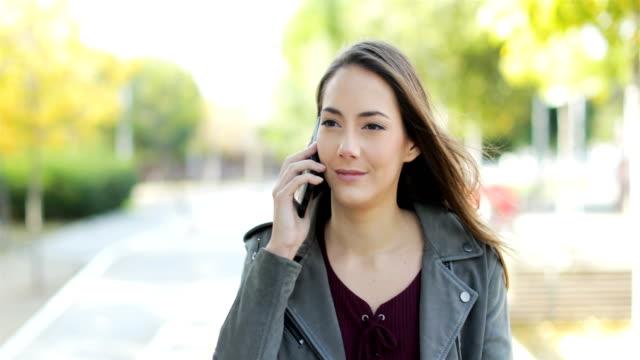 woman walking and talking on phone in a park - ear talking video stock e b–roll