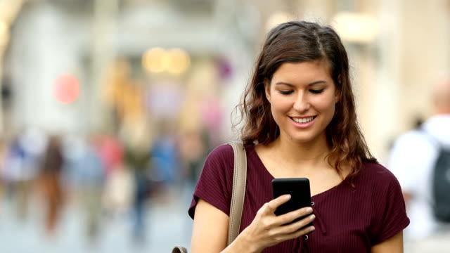 vidéos et rushes de une femme marchant et en utilisant un smartphone dans la rue - message