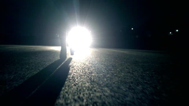 Woman walking at night in front of car light Woman walking at night in front of car light alley stock videos & royalty-free footage