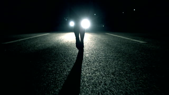 Woman walking at night in front of car light