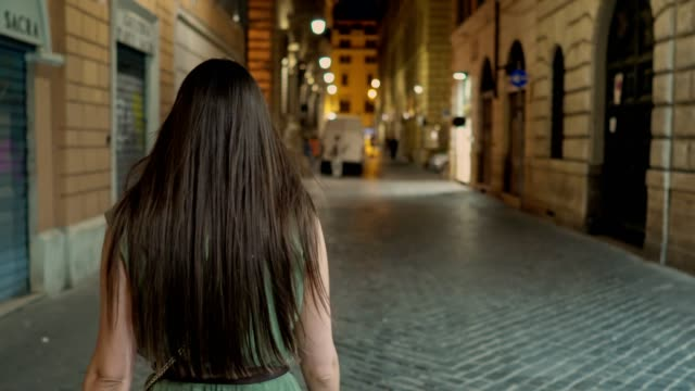 Woman walking at the streets of Rome by night