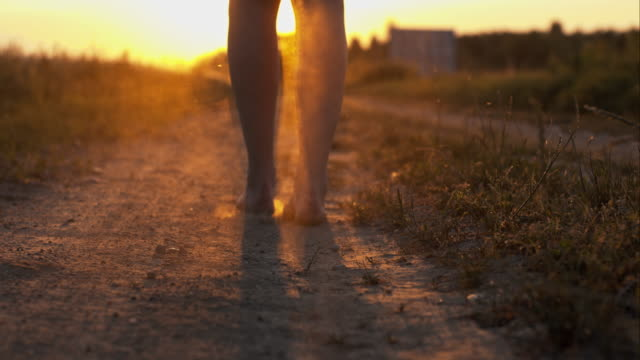 Woman walking barefoot on a dirt road video