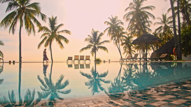 vídeos de stock e filmes b-roll de ws woman walking by the pool of a luxury resort - luxo