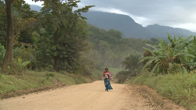 woman walking down a lonely dirt road in africa dirt road in africa, with single woman walking tanzania stock videos & royalty-free footage