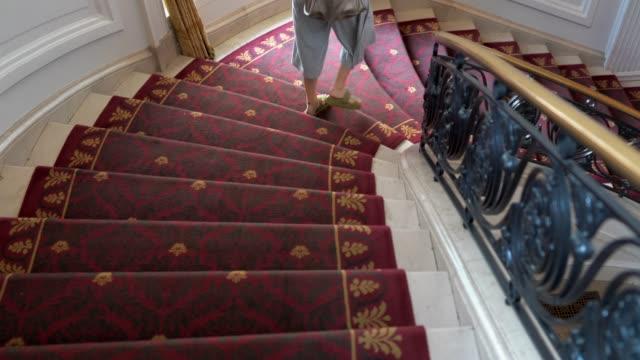 woman walking down spiral stair case
