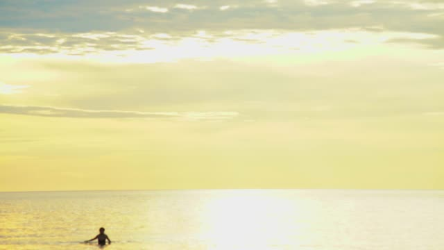 woman walking from the sea with bright gold colour sky background cinemagraph 4K loopable
