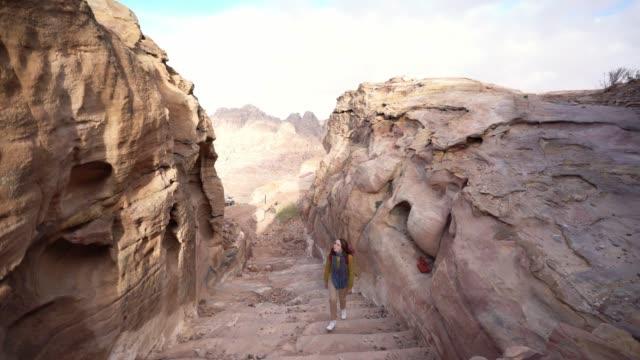 vídeos y material grabado en eventos de stock de mujer caminando en cañón en petra - estrecho