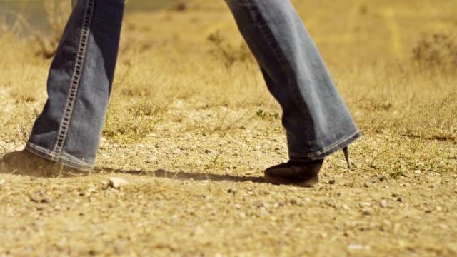 donna camminare nel deserto. stile western. con una videocamera in movimento. colpo del drago rosso epica digitale cinema macchina fotografica. - arto inferiore animale video stock e b–roll