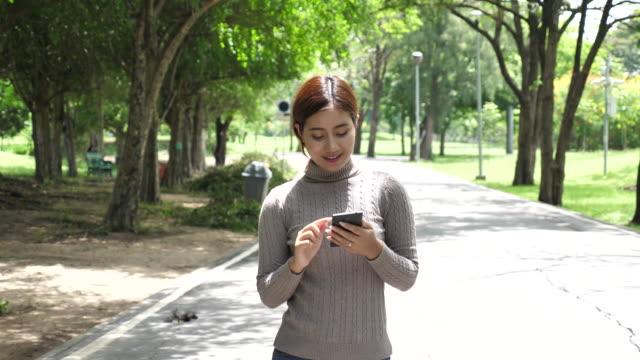 公園で使用するスマート フォンを歩く婦人 - スマートフォン点の映像素材/bロール