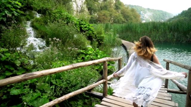 woman walking in plitvice lake national park - национальный парк плитвицкие озёра стоковые видео и кадры b-roll