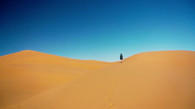 Frau zu Fuß in der Wüste Sahara bei Sonnenuntergang – Video