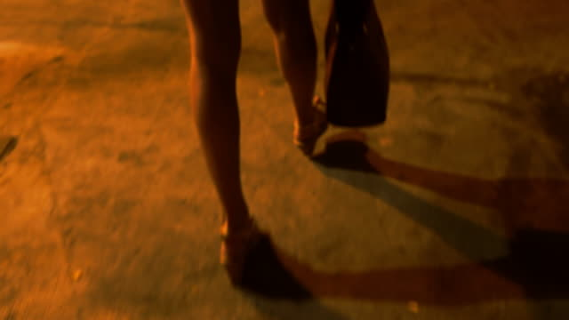 Woman walking in the city at night video