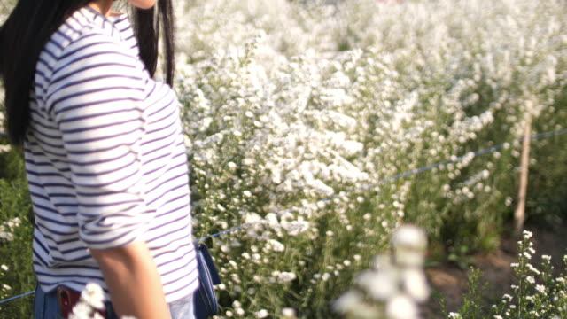 Woman walking in the field of White flower