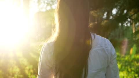 vidéos et rushes de femme marchant dans la forêt au coucher de soleil. ralenti - marcher
