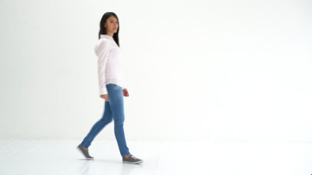 Woman walking into a white background studio and showing something video