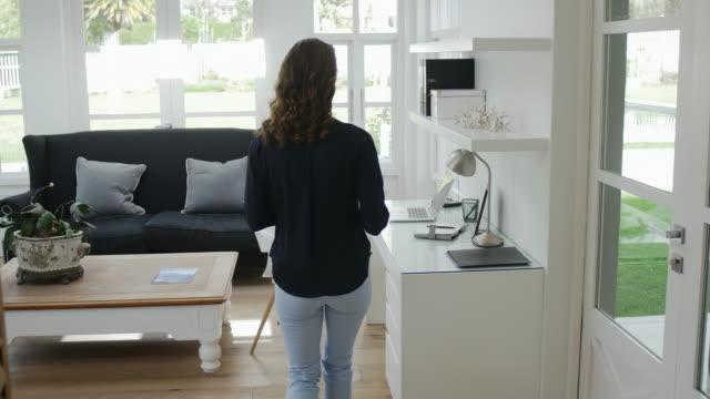 woman walking into modern home office - studio camera video stock e b–roll