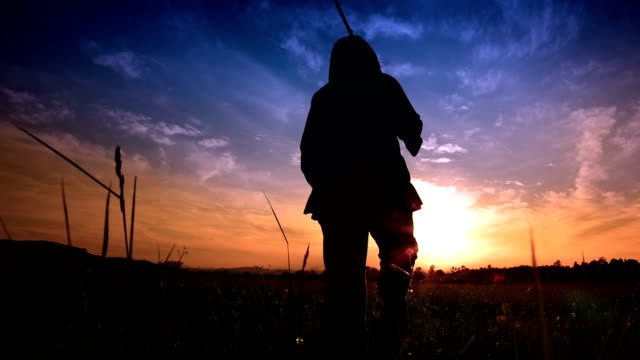 hd - woman walking into sunset with rifle - hunting stock videos and b-roll footage