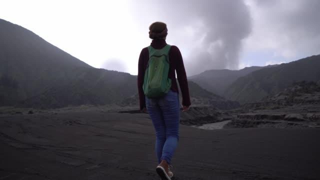 Woman walking near Bromo volcano at sunrise