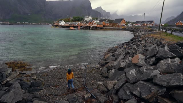 Woman walking near fjord in village in Lofoten Islands